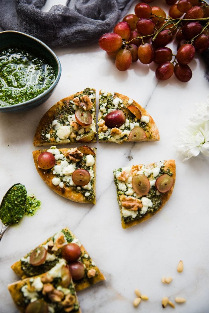 pita pizza with kale pesto on a marble white board