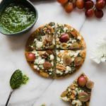 pita pizza made on pita bread with kale pesto, walnuts and red grapes