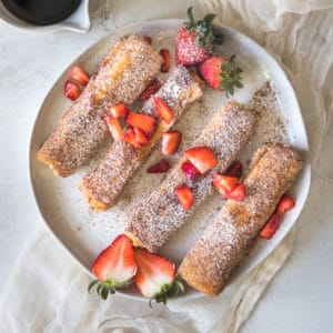 french toast on a white plate with strawberries
