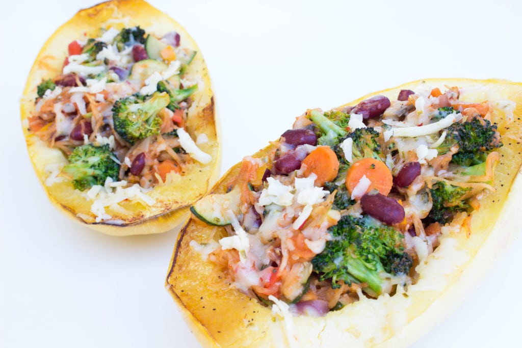 spaghetti squash on a white board filled with veggies and cheese