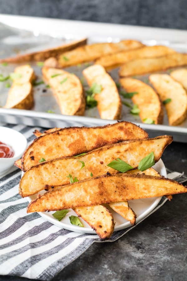 homemade potato wedges on white plate