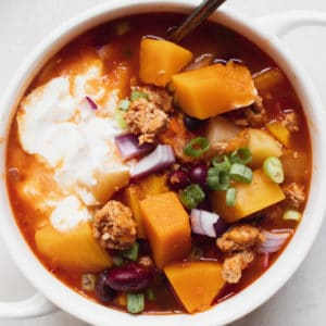 chili in a white soup bowl topped with green onions and sour cream