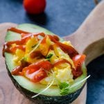 Scrambled eggs in an avocado topped with tomatoes and Sriracha