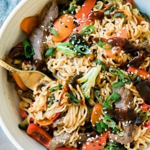 stir fry in a white bowl with steak and ramen noodles