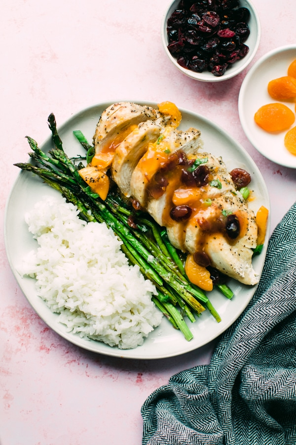 chicken on a white plate with rice and asparagus