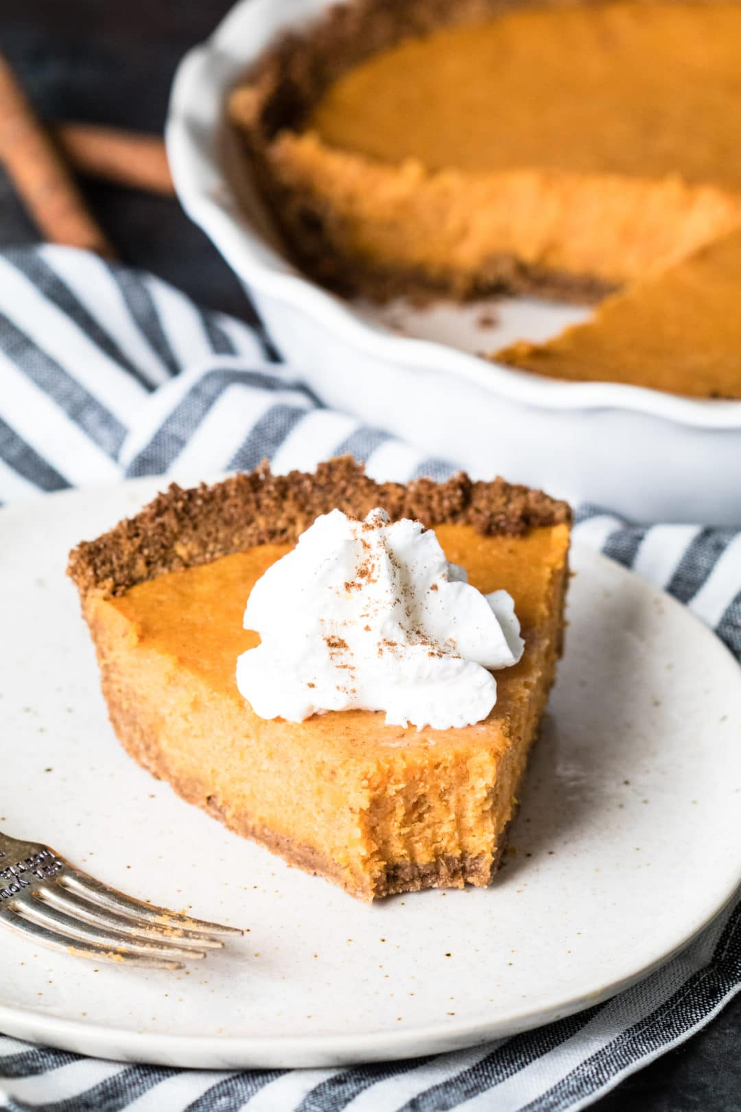 Sweet potato pie on a plate topped with whipped cream.