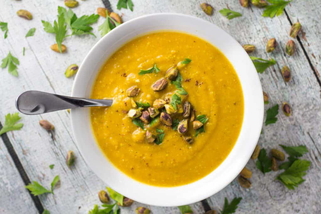 Pistachio and Pumpkin soup in a white bowl