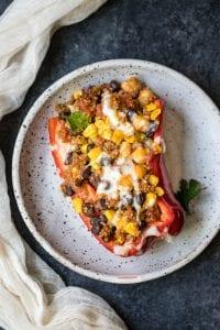 quinoa and veggies stuffed in a red bell pepper