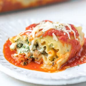 lasagna roll up on a white plate topped with cheese