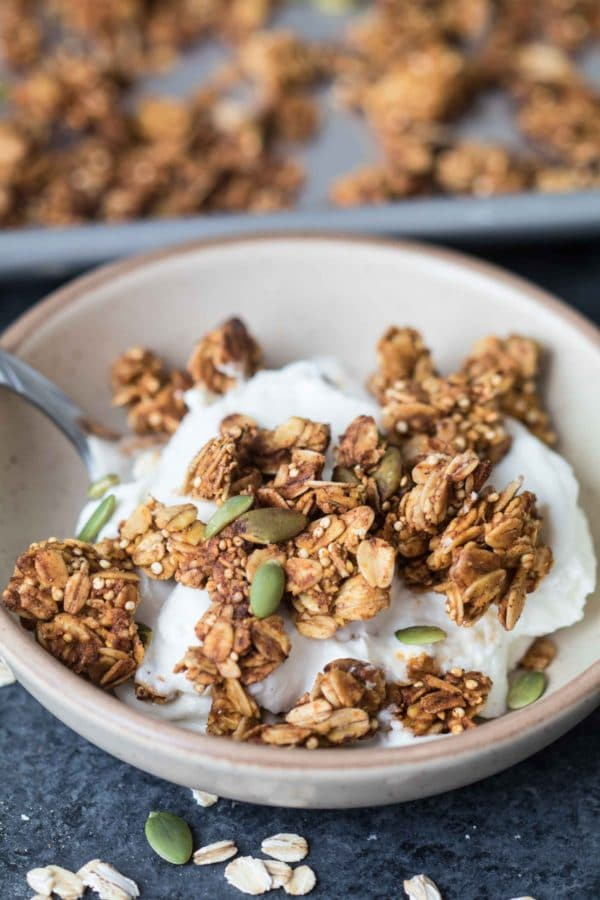 Yogurt in a bowl with a spoon and pumpkin spice granola on top