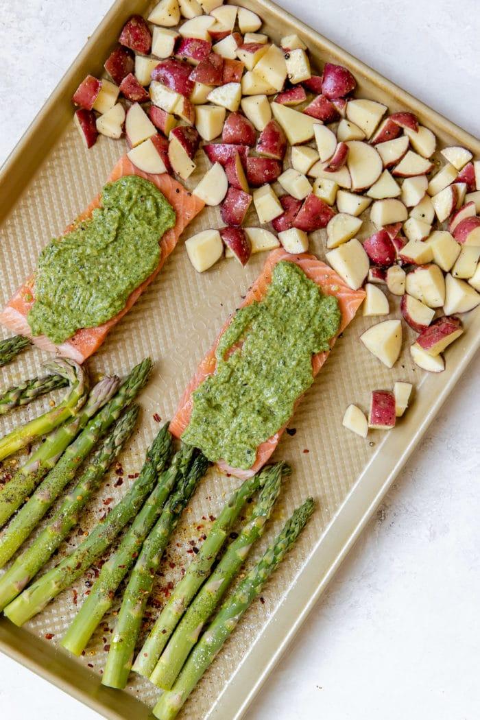 salmon with veggies on a gold sheet pan