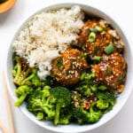 meatballs in a white bowl with broccoli and rice
