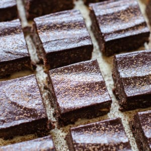 brownies on parchment paper dusted with cocoa powder