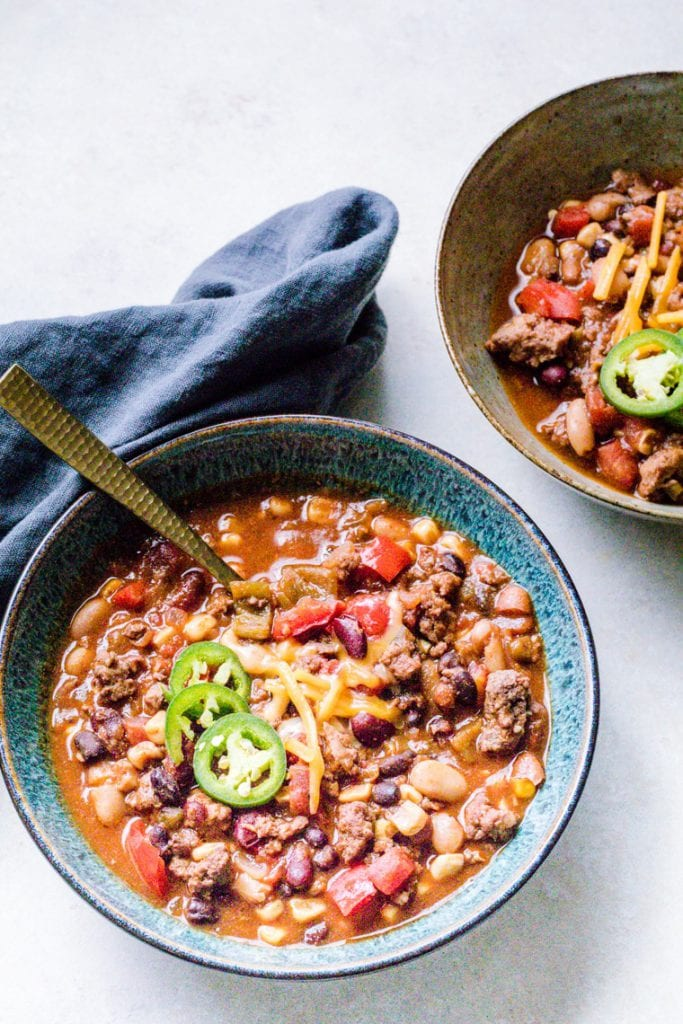 Lamb Chili in a bowl topped with jalapenos with a grey napkin on the side