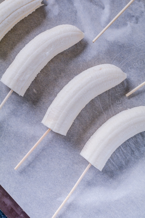 Bananas cut in half on a stick placed on a cookie sheet