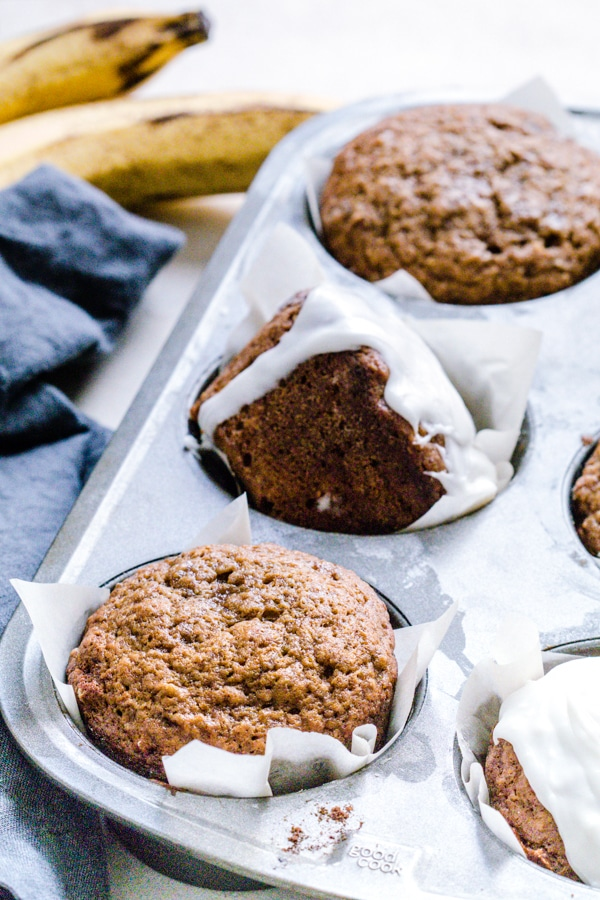 Muffins in a muffin tin with ripe bananas on the side.