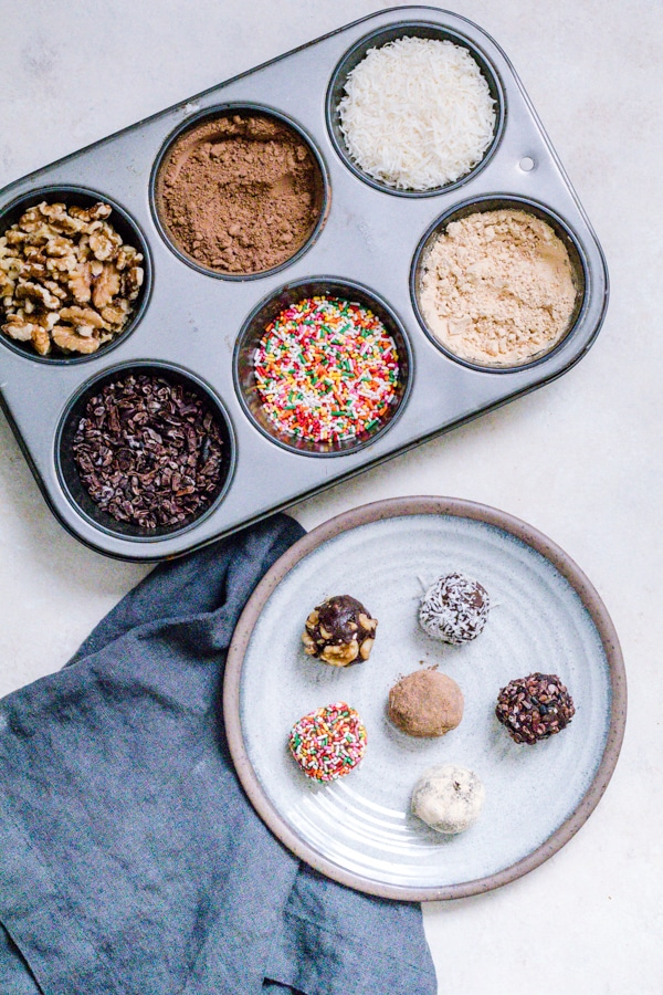 Decorated No Bake Pumpkin Brownie Bites on a plate with the toppings on the side in a muffin tin.