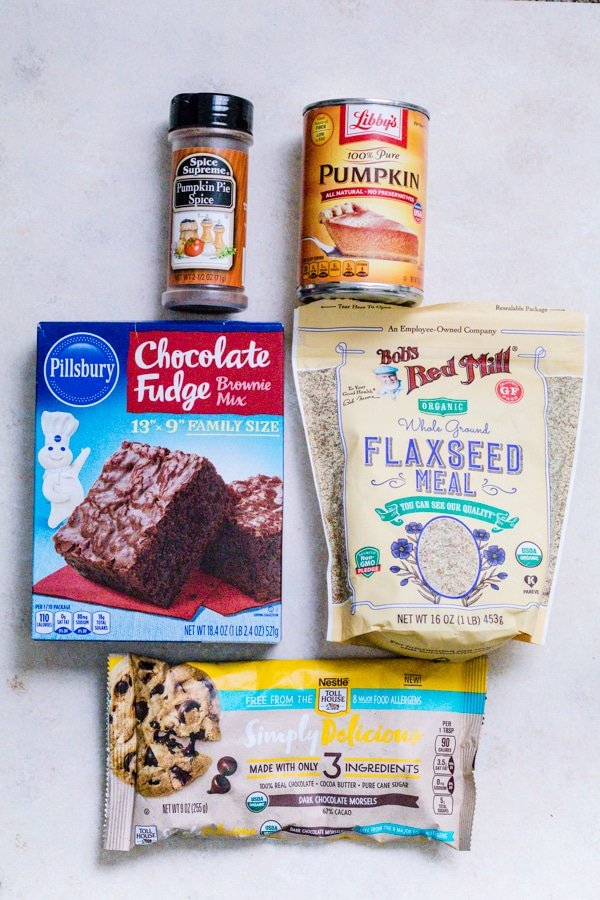 Ingredients for no bake pumpkin brownie bites - pumpkin pie spice, pumpkin puree, brownie mix, flaxseed, and chocolate chips