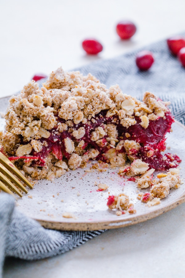 Cranberry oat crumble on a plate with a gold fork