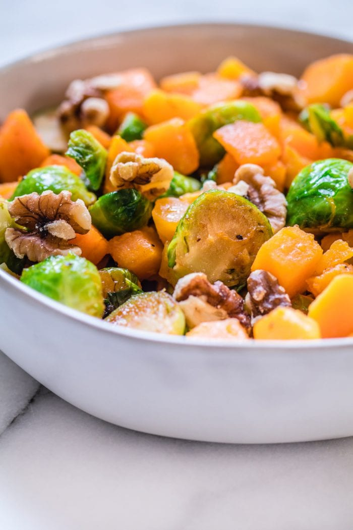butternut squash and brussels sprouts in a bowl on a marble bowl.