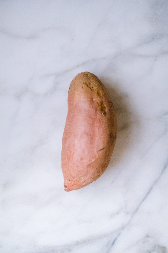 Sweet potato, not cooked, on a marble board
