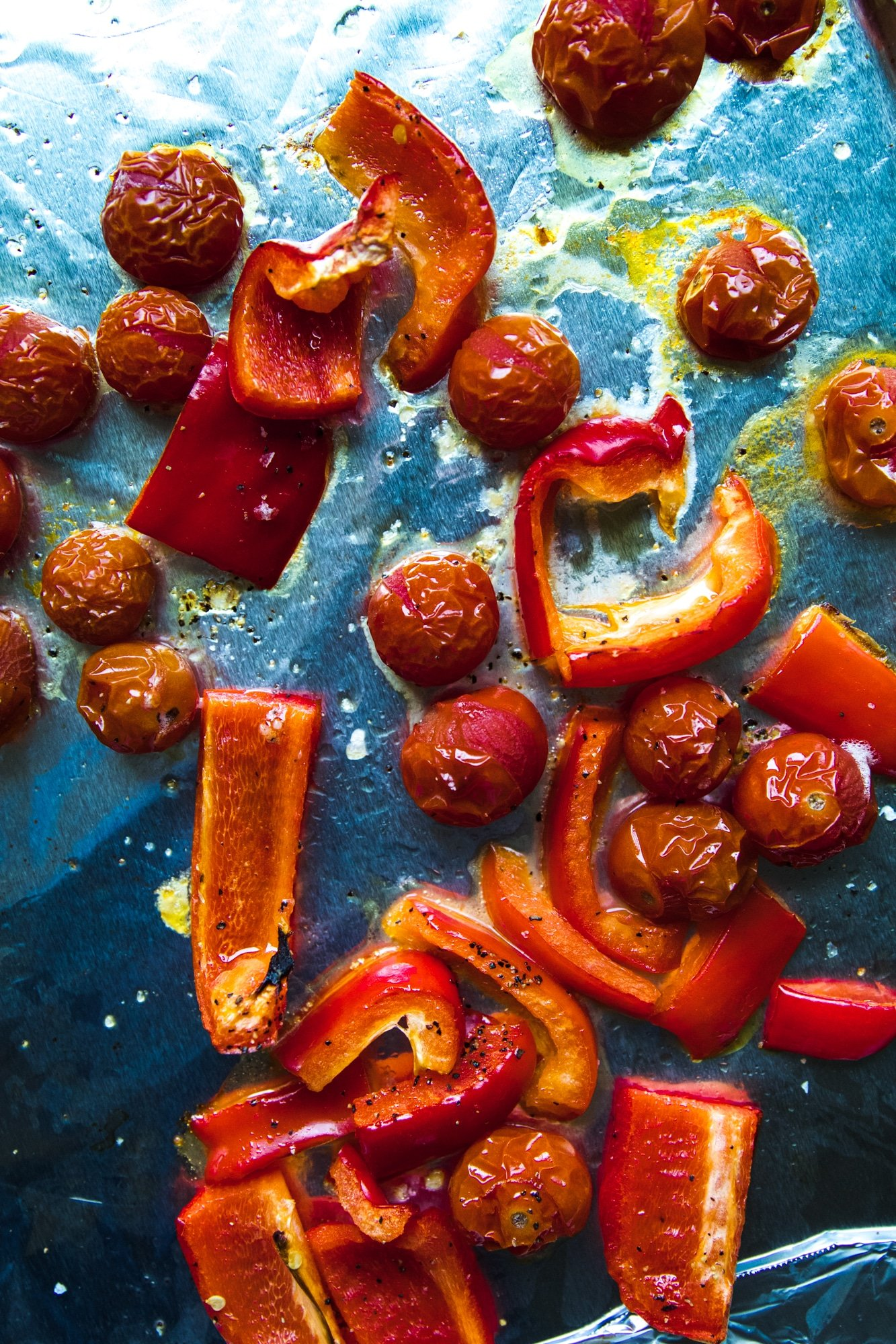 roasted bell peppers and tomatoes on a sheet pan