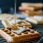 waffles with butter in the middle and maple syrup pouring on the waffle