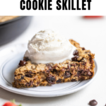 a slice of an oatmeal raisin chocolate chip cookie skillet on a white plate with vanilla bean ice cream