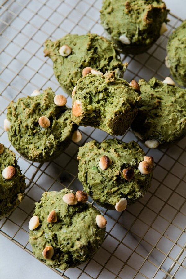Muffins made with matcha and avocado on a cooling rack.