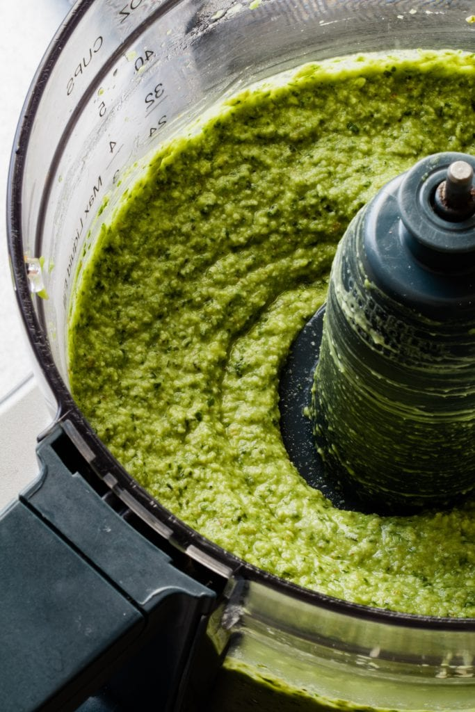 avocado pesto sauce being blended in a food processor