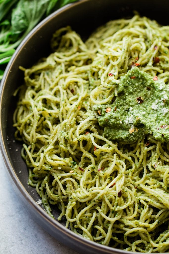 avocado pesto sauce tossed in angel hair pasta in a black bowl