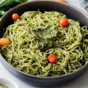 Pasta with pesto sauce in a bowl with cherry tomatoes