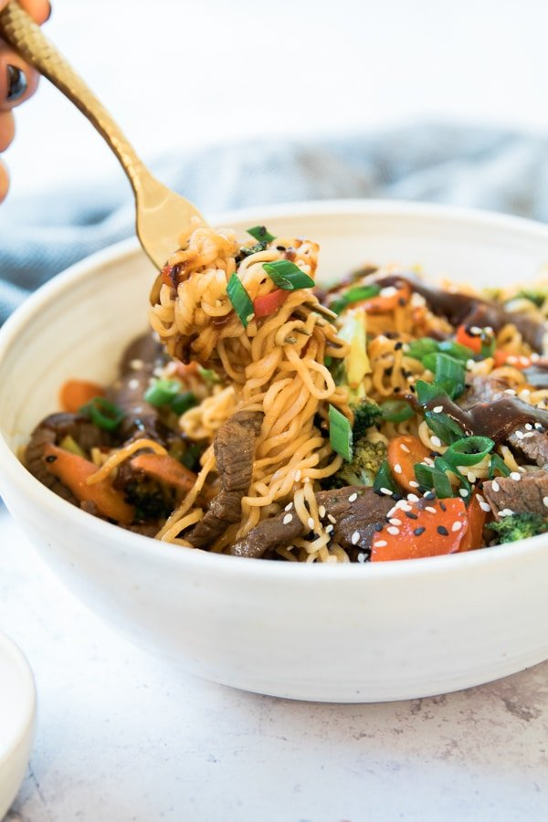 beef and veggie stir fry with a gold fork in a white bowl