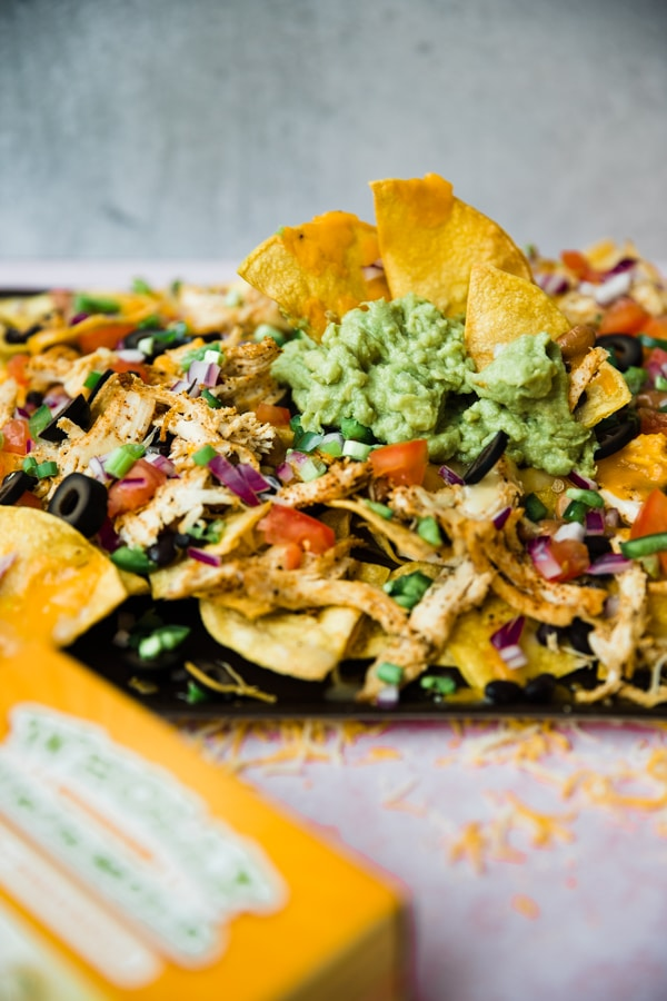 sheet pan chicken nachos with guacamole on top