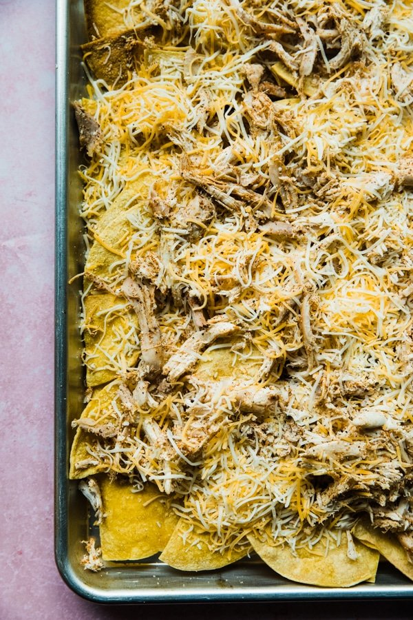 sheet pan chicken nachos topped with cheese