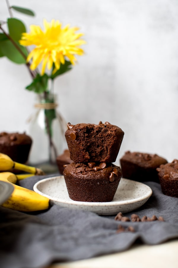 chocolate chia banana muffins on a white speckled plate