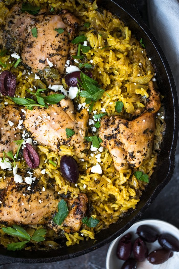 mediterranean chicken and yellow rice in a cast iron skillet