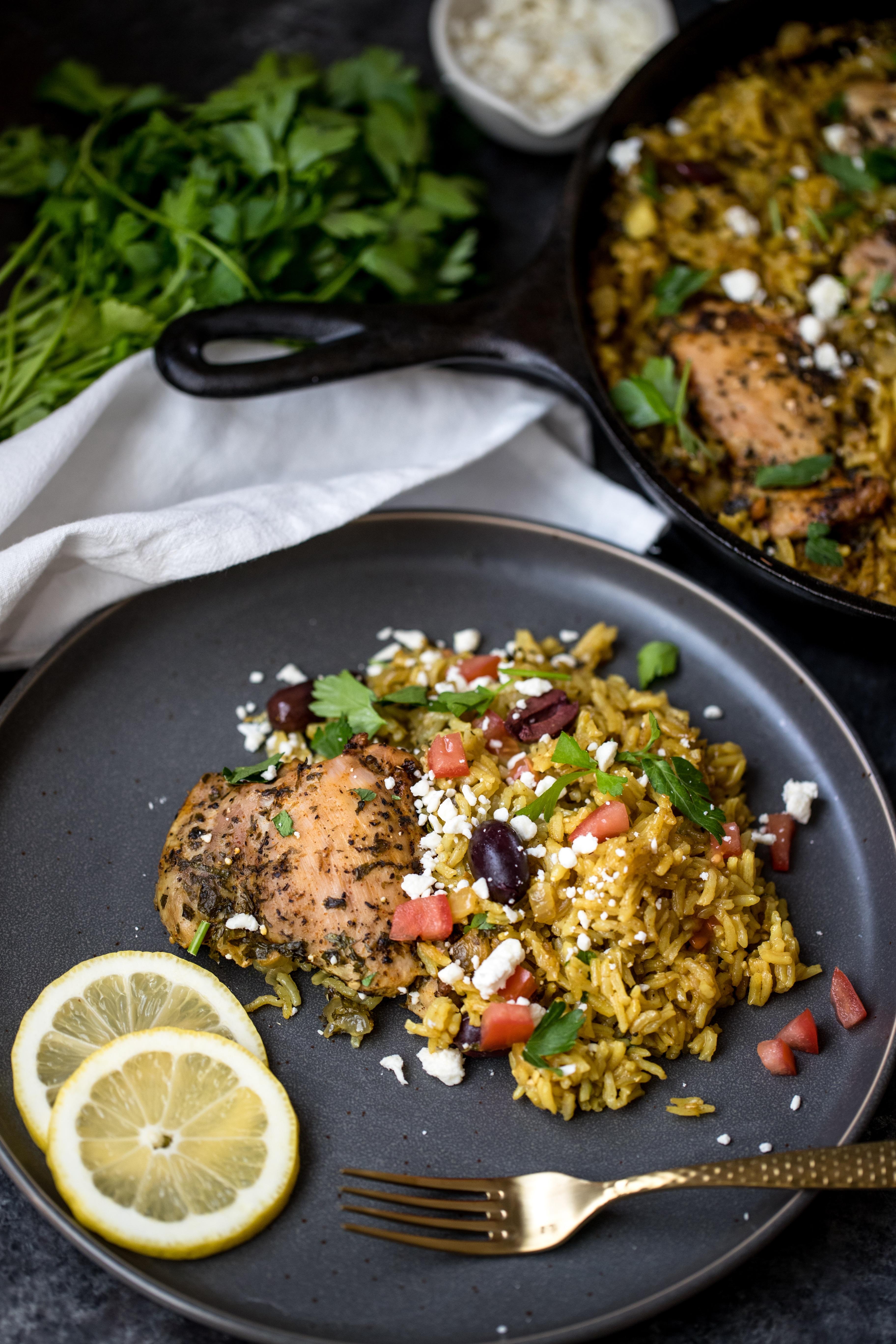 mediterranean chicken and rice on a dark grey plate