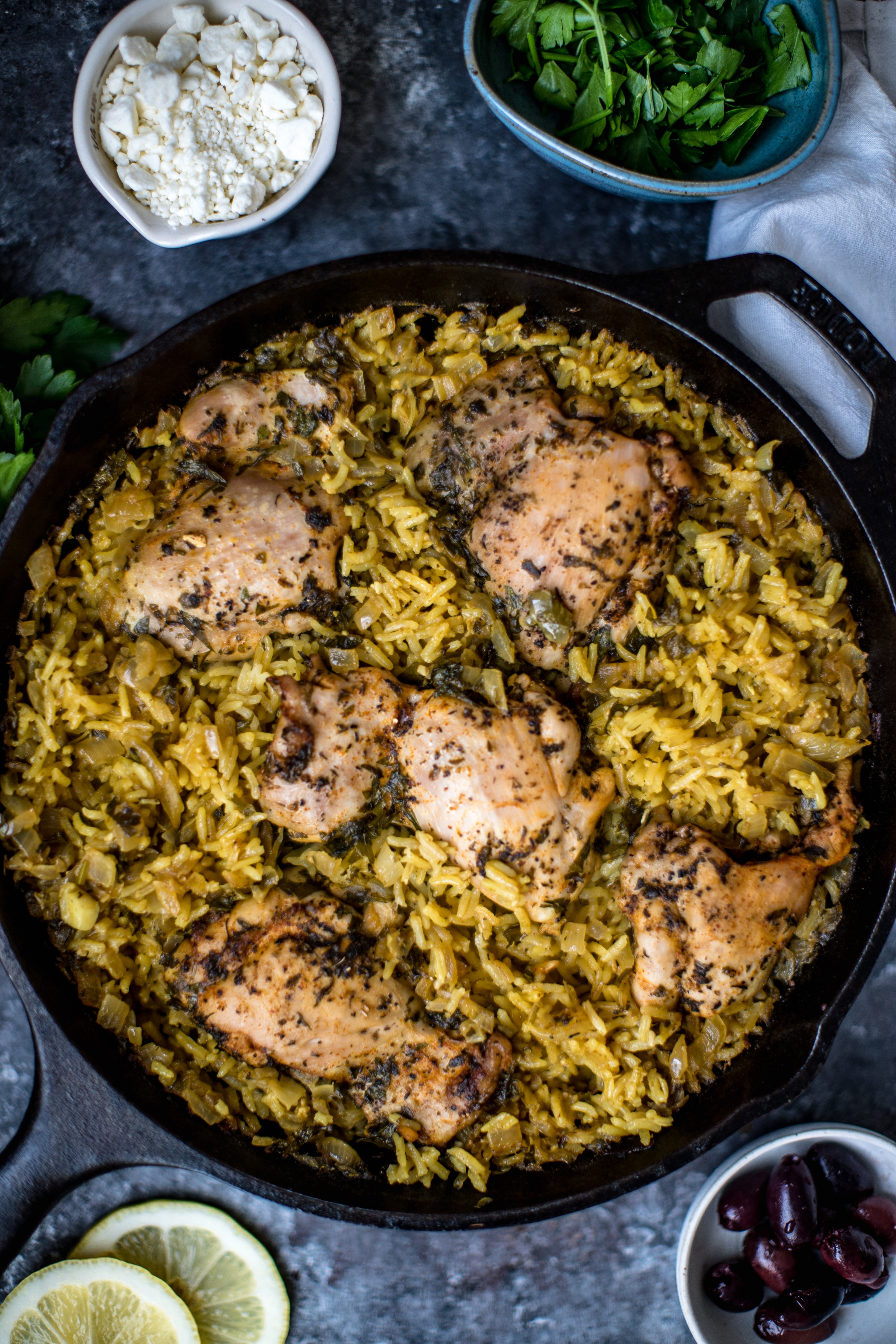 a cast iron skillet filled with rice and chicken