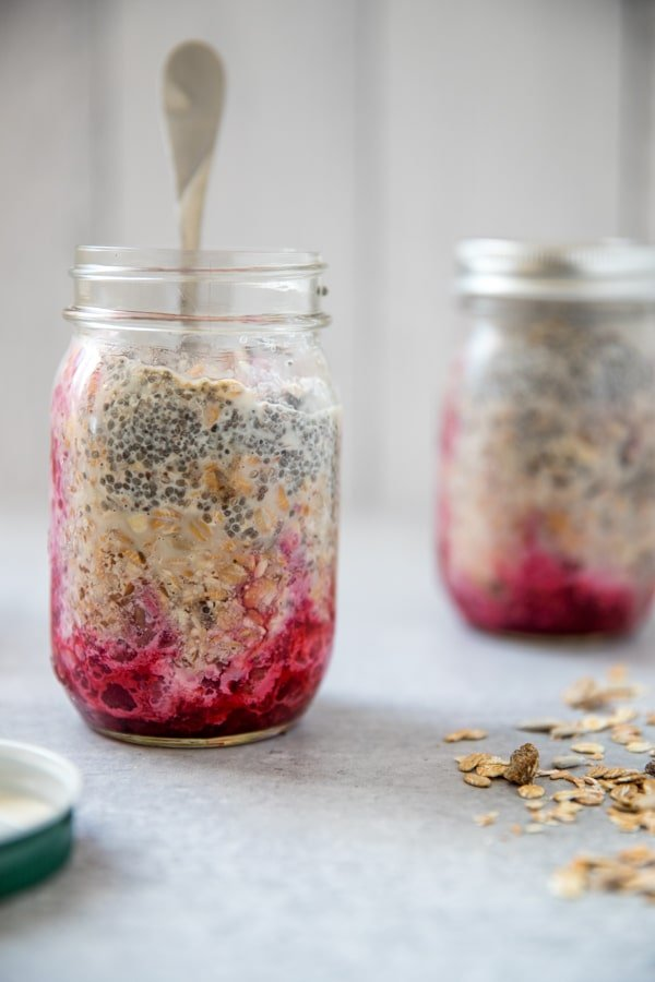 prepping overnight muesli in a mason jar with the fruit on the bottom