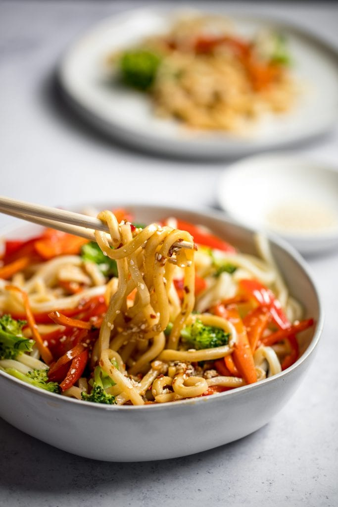 sesame udon noodles with veggies in a white bowl