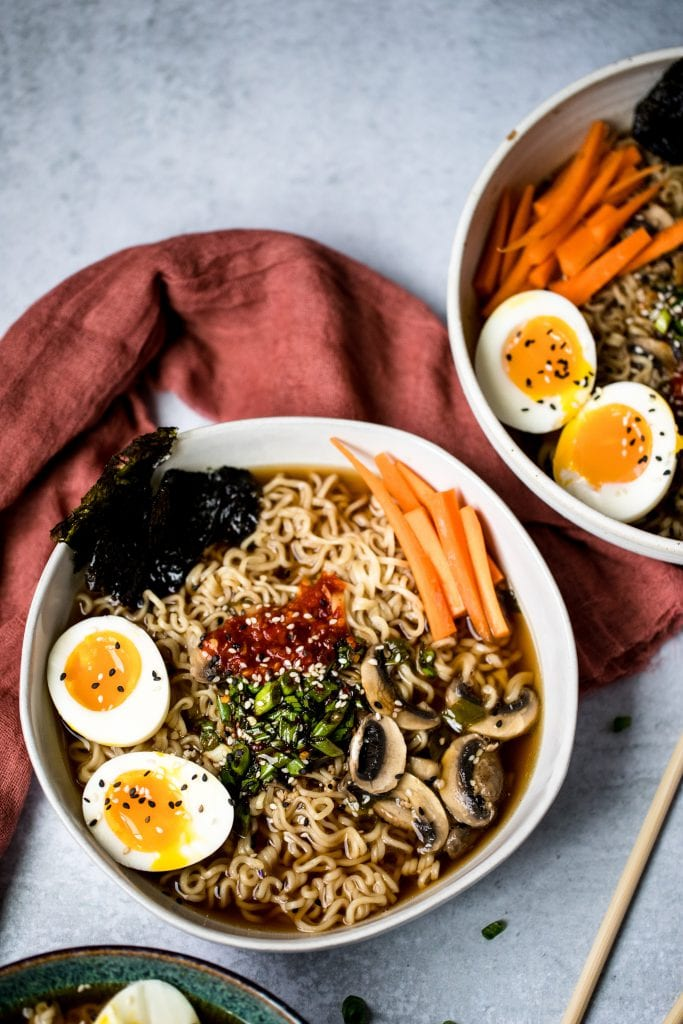 two bowls of vegetarian ramen topped with soft-boiled eggs, sliced carrots, seaweed, and green onions