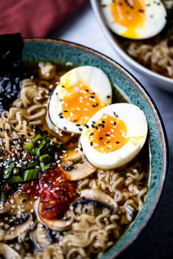 vegetarian ramen topped with soft boiled eggs, carrots, mushrooms, and broth