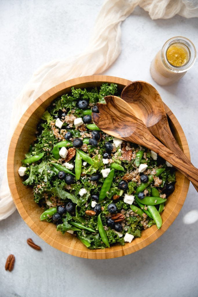 kale blueberry salad in a large wooden bowl