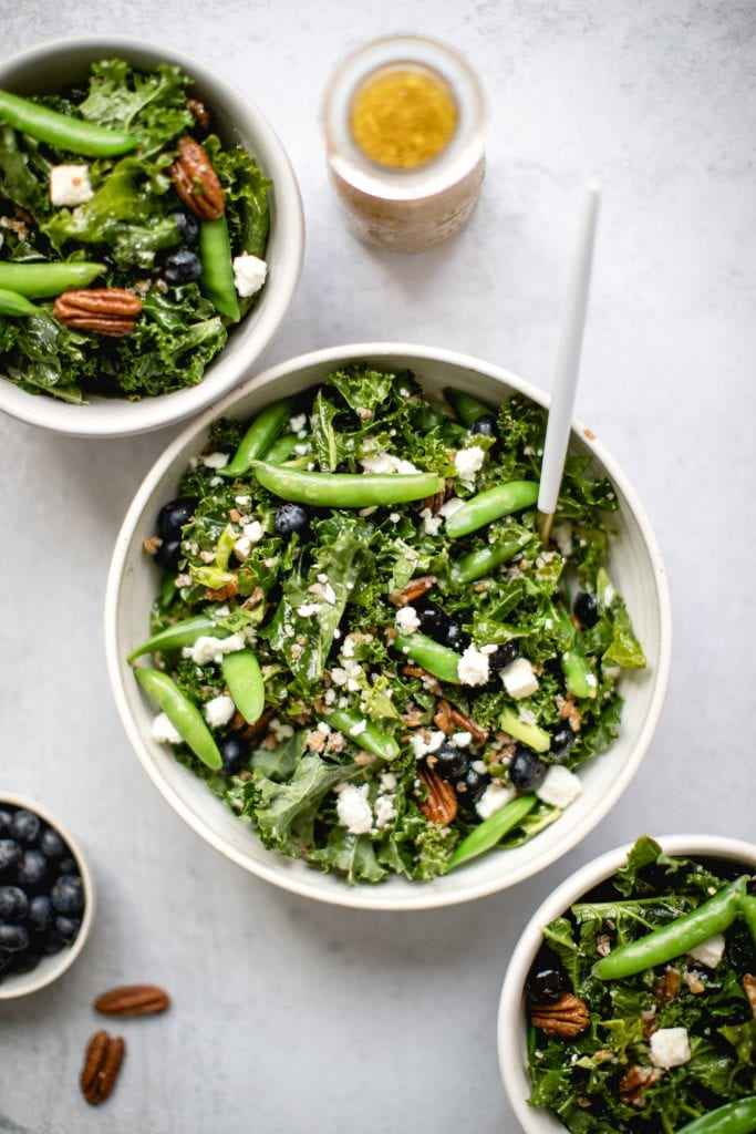 kale salad with blueberries in a large white bowl