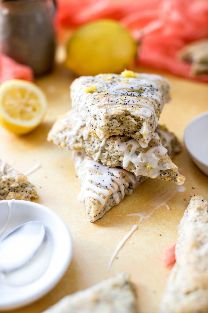 lemon poppyseed scones with a lemon glaze on top on a yellow board