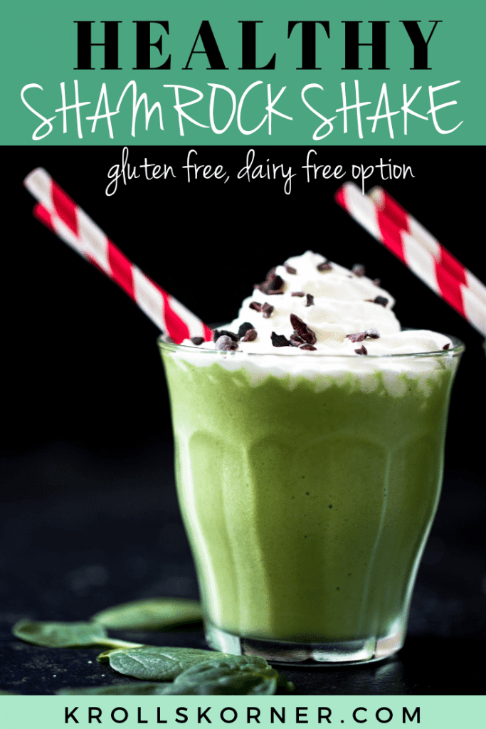 a green smoothie in a glass cup topped with whipped cream and red straws