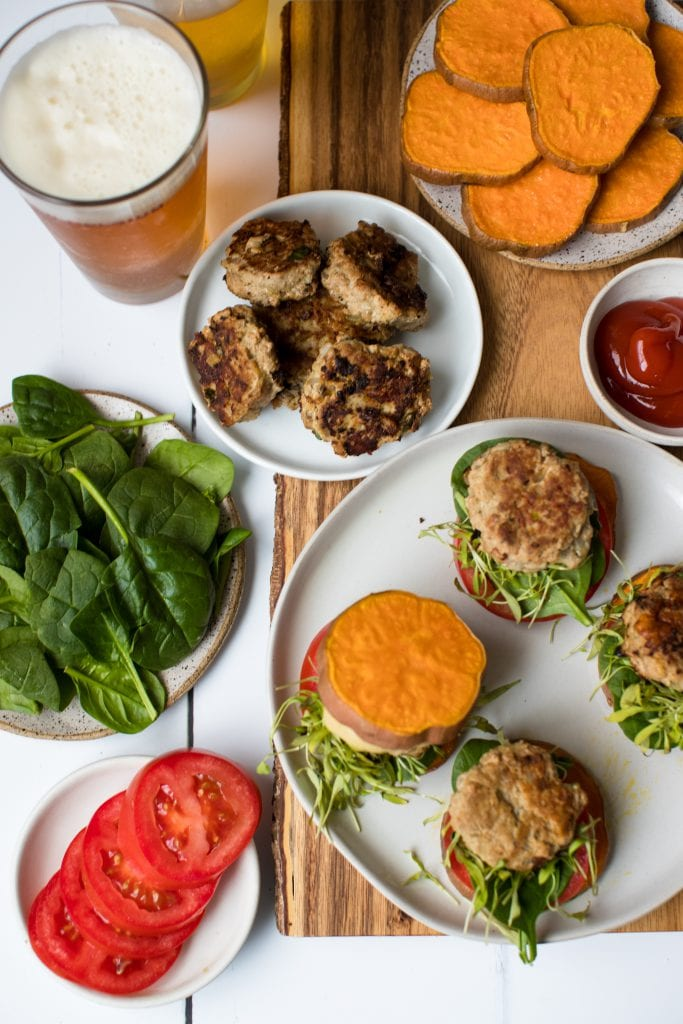 a turkey burger on a white plate with sweet potato