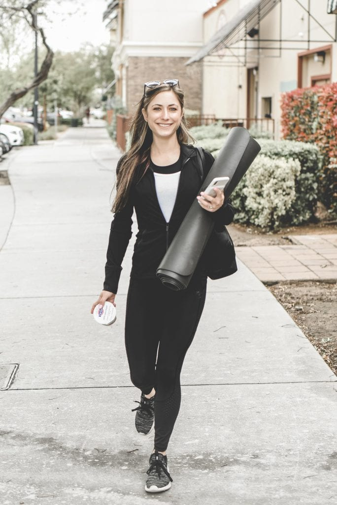 A woman walking down a sidewalk