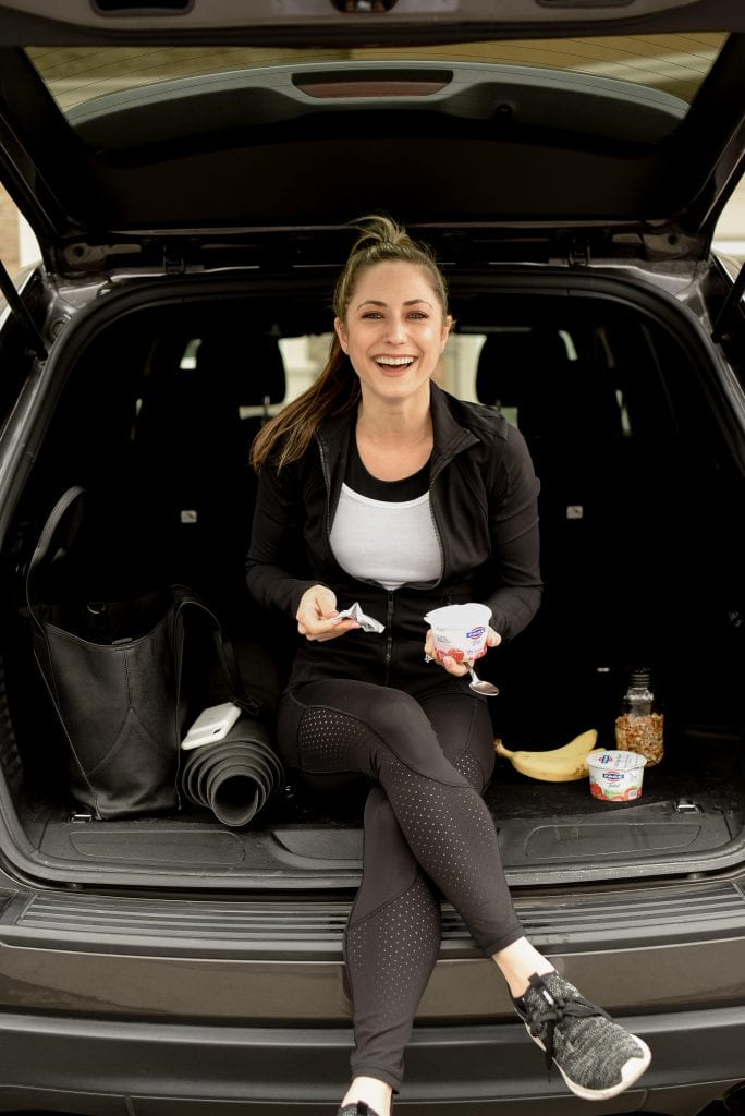 A woman sitting in the backseat of a car with yogurt